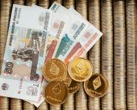 Złociste crypto monety Ethereum ETH, papierowi wyznania Rosyjscy ruble Metal monety kłaść out w gładkim tle each inny Zdjęcia Stock