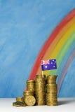 Złociste dolar australijski monety przeciw niebieskiego nieba i tęczy plecy Fotografia Royalty Free