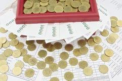 Złociste monety na czerwonym skarbie boksują i rachunki Fotografia Stock
