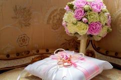 Złociste obrączki ślubne kłamają na dekoracyjnej jedwabniczej poduszce z różowymi atłasowymi faborkami obok panna młoda bukieta obraz stock