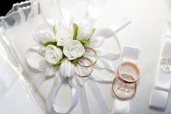 Złociste obrączki ślubne na poduszce z faborkiem i kwiatami Obrazy Royalty Free