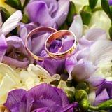 Złociste obrączki ślubne na bukiecie kwiaty Zdjęcia Royalty Free