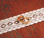 Złociste obrączki ślubne na drewnianym tle Zdjęcia Royalty Free