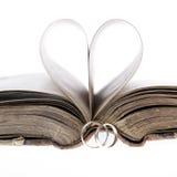 Złociste obrączki ślubne, stara książka i papieru serce, Fotografia Royalty Free