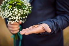Złociste obrączki ślubne w panny młodej ` s ręce w kostiumu z bukietem kwiaty biały kolor zdjęcie stock