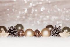 Złociste piłki na złotym świateł bożych narodzeń tle Fotografia Stock