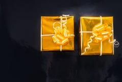 Złocistej folii zawijający Bożenarodzeniowi prezenty na czerni obraz royalty free