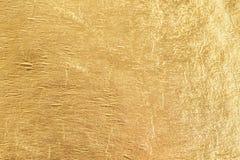 Złocisty błyszczący foliowy tło, żółtej glosy kruszcowa tekstura zdjęcie royalty free