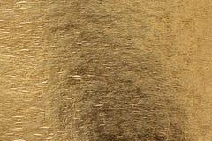Złocisty błyszczący foliowy tło, żółtej glosy kruszcowa tekstura zdjęcia royalty free