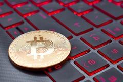 Złocisty bitcoin na klawiaturze z czerwoną iluminacją zdjęcia royalty free