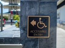 Złocisty i czarny dostępny wejście znaka przeniesienie z wózka inwalidzkiego foru logo z strzałą wskazuje lewica obraz stock