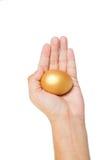 Złocisty jajko w ręce odizolowywającej na bielu Obrazy Royalty Free