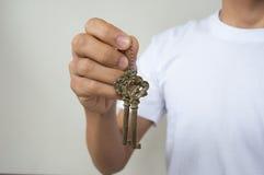 Złocisty kluczowy łańcuch z kluczem wewnątrz wręcza mężczyzna Obrazy Stock