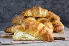 Złocisty masła croissant smarujący z masłem na naturalnej drewnianej desce obrazy stock