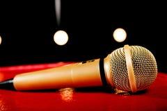 Złocisty mikrofon na ciemnym tle z dużo zaświeca Fotografia Royalty Free