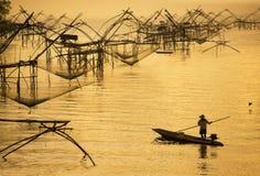 Złocisty oświetlenie z rybakiem i dużą kwadratową upad siecią Fotografia Royalty Free