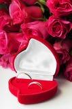 Złocisty pierścionek w czerwonym aksamita pudełku z różami na białym tle fotografia stock