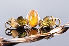 Złocisty pierścionek z bursztynem i kolczykami z zielonymi kamieniami Obrazy Royalty Free