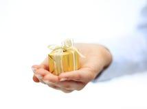 Złocisty prezenta pudełko w ręce z faborkiem odizolowywającym na białym backgraund Zdjęcie Stock