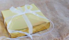 Złocisty prezenta pudełko z białym faborkiem na brązu worku fotografia royalty free