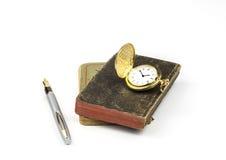 Złocisty zegarek i pióro z starymi książkami fotografia royalty free