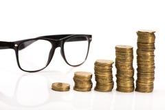 złocistych monet sterta i czarni szkła odizolowywający Zdjęcie Stock