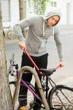 Złodziej próbuje łamać rowerowego kędziorek fotografia stock