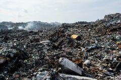 Złomowy rozsypisko przy śmieciarskim usypem pełno dym, ściółka, klingeryt butelki, banialuki i grat przy tropikalną wyspą, obrazy stock