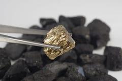 Złota bryłka na węgla tle Obraz Stock