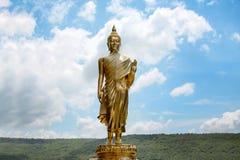 Złota Buddha postaci pozycja z chmurnym niebem fotografia stock