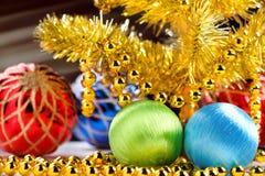 Złota choinka z dekorującymi lekkimi promieniami na ciemnym tle i piłkami Obrazy Stock