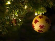 Złota dekoracyjna piłka z czerwonymi błyszczącymi ornamentami wiesza na choince zdjęcia royalty free