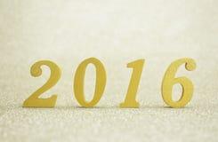 Złota drewniana liczba 2016 nad złocistym tłem Fotografia Stock