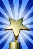 Złota gwiazdowa nagroda na stojaku przeciw jaskrawemu błękitnemu tłu Obraz Royalty Free
