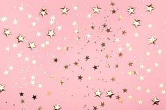 Złota gwiazdy błyskotliwość na różowym tle obrazy stock