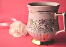 Złota i menchii porcelany herbaciana filiżanka i spodeczek z rzemieślnik czekoladą na jaskrawym fuksj menchii tle z kopii przestr Obraz Royalty Free