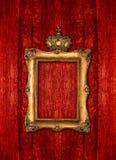 Złota rama z koroną nad czerwonym drewnianym tłem Obrazy Stock