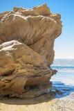 Złota skała w seashore z jasnym niebieskim niebem widzieć od ri Fotografia Royalty Free