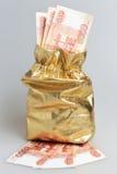 Złota workowy pełny pieniądze na szarość Zdjęcia Royalty Free