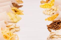 Złote kolorowe przekąski - nachos, popkorn, croutons, układy scaleni w rzemiosło papieru rożku jak granicę na białym drewno stole Zdjęcia Stock