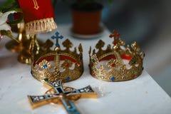 Złote korony i obrączki ślubne przy ołtarzem w kościół przy ślubną parą tradycyjna religijna ślubna ceremonia zdjęcie stock