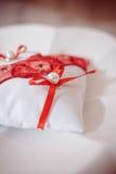 Złote obrączki ślubne na czerwonej karmazynów i bielu ringowej poduszce z Obrazy Stock