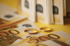 Złote obrączki ślubne na euro banknotu tle Małżeństwo dogodność zdjęcie royalty free