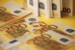 Złote obrączki ślubne na euro banknotu tle Małżeństwo dogodność fotografia stock