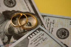 Złote obrączki ślubne na sto dolarach rachunku tła zdjęcia royalty free