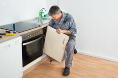 Złotej rączki naprawiania zlew drzwi W kuchni fotografia stock