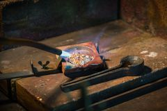 Złotnik złociste i srebne roztapiające granule w tyglu z a zdjęcie royalty free