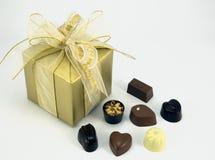 Złoto teraźniejszy z asortowanymi czekoladami. Obrazy Royalty Free