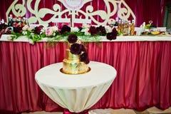 Złoty ślubny tort z wyśmienicie kwiatami przy małym stołem zdjęcie royalty free