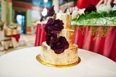 Złoty ślubny tort z wyśmienicie kwiatami przy małym stołem fotografia royalty free